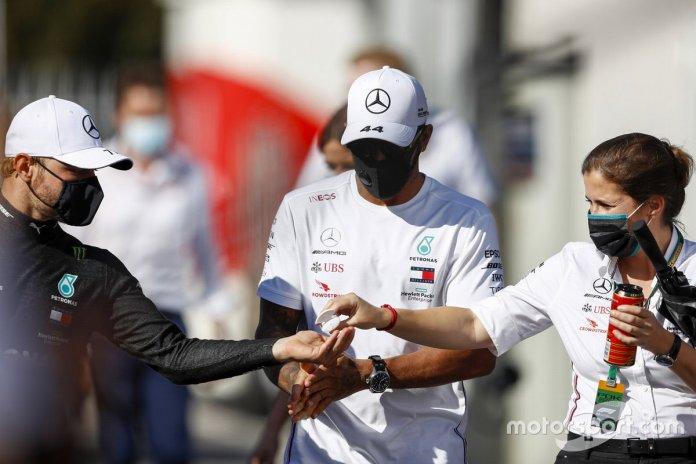 Lewis Hamilton, Mercedes-AMG F1, y Valtteri Bottas, Mercedes-AMG F1, se desinfectan las manos