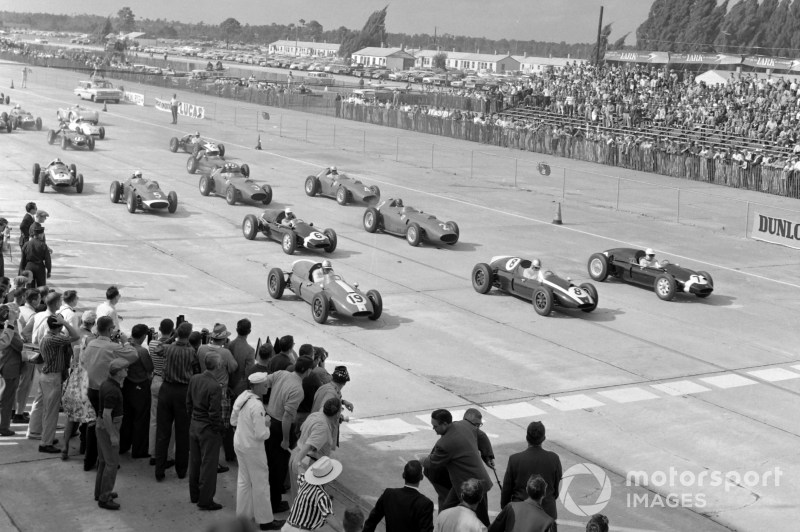 Stirling Moss, Cooper T51 Climax, Jack Brabham, Cooper T51 Climax, and Harry Schell, Cooper T51 Climax, lead the field away at the start.