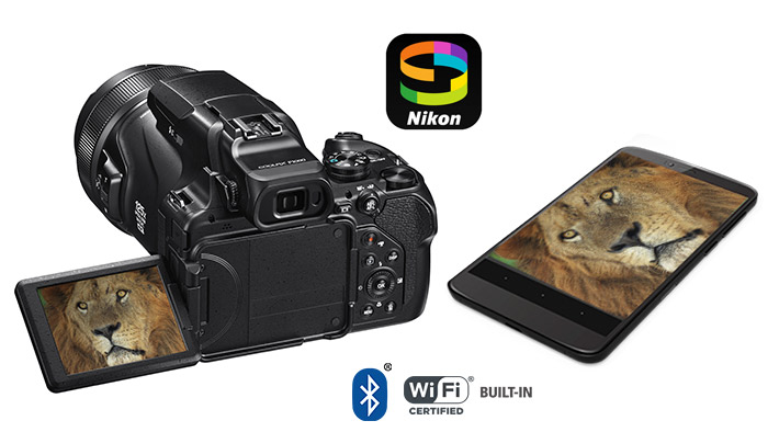 Photo of the COOLPIX P1000 and a smartphone with a photo of a lion's face on the LCD and phone screen, and the SnapBridge logo