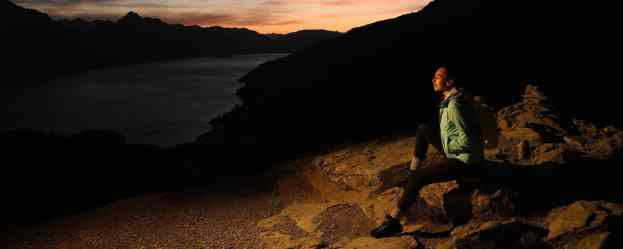 Photo of a person sitting on rocks in low light