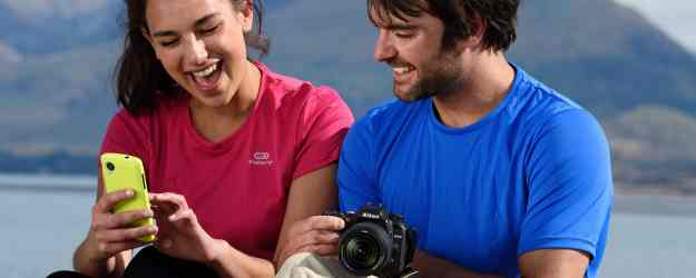 photo of a woman holding a smartphone and a man holding the D7500