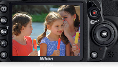 Close up photo of the D3100's LCD with the buttons on the camera showing,   with an image of three girls eating ice pops on the LCD