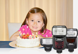 Photo of a little girl with a birthday cake inset with a grouping of three Nikon flashes (Speedlights)