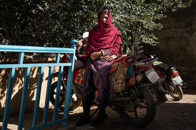 a man sitting on a motorbike while waiting in front of the maternity department at the Tangi Saidan clinic.
