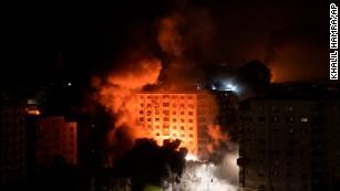 Smoke caused by Israeli airstrikes are seen at a residential building in Gaza City.
