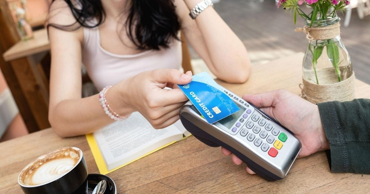Woman using a credit card with the contactless payment symbol to make a purchase at a cafe