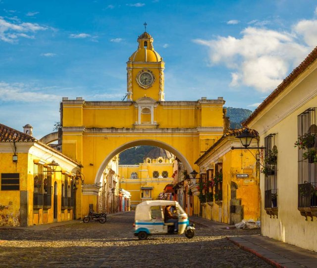 A Tuk Tuk Taxi Passes In From Of The Arch Of Santa Catalina In Antigua