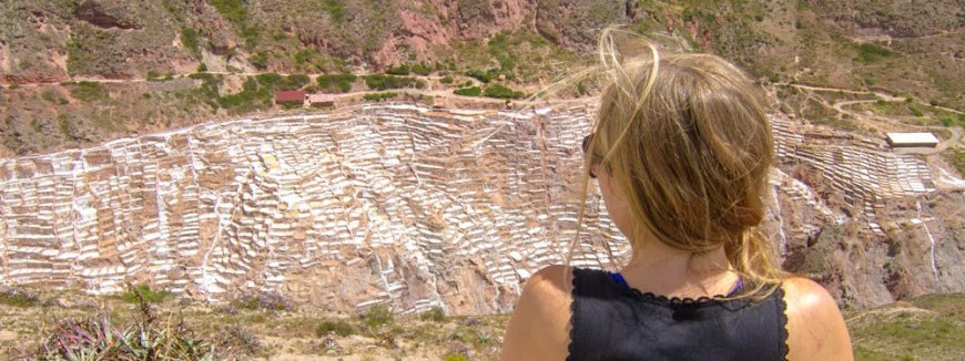 Best Hikes In Peru Image: A woman with a blonde braid pulled over her right shoulder is wearing a black top, sunglasses, and is observing the salt mines from across the valley.