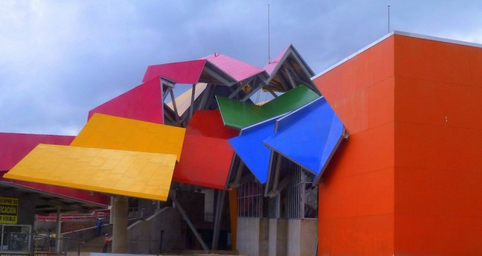 Architecture In Panama Image: An angle of Panama's Frank Gehry designed building shows yellow, magenta, pink, blue, red, and green surfaces at different angles and compositions.