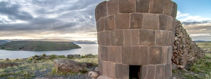 Best Hikes In Peru Image: Photograph of a funerary tower with an opening; this particular tower is overlooking the water.