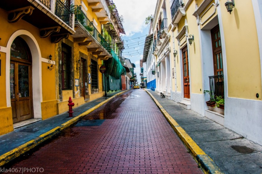 Architecture In Panama Image: A narrow city street is lined with buildings on both the left and right. We can see shades of mustard yellow, pale lemon, turquoise, and marine blue gracing their faces. Many have wrought iron balconies.