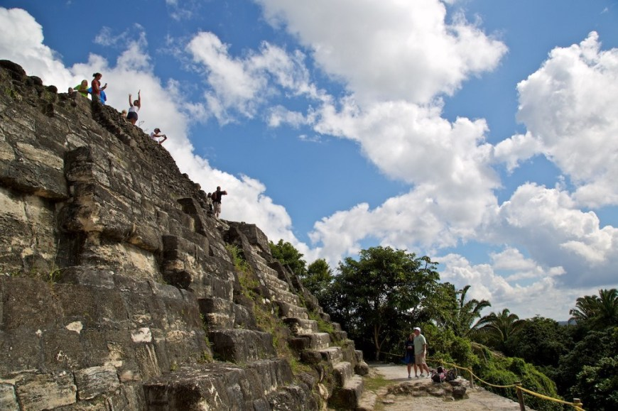Central and South American Ruins Image: A group of travellers celebrates having reached the top of the temple. Whilst a couple admires them, and considers making the walk themselves.