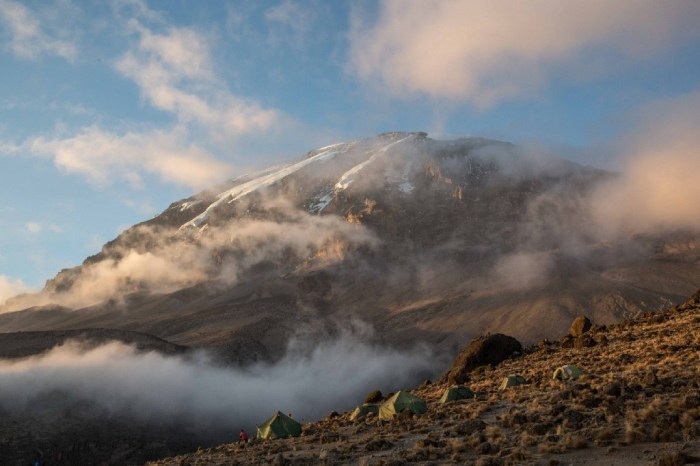 Destinations Worth Dreaming Image: Morning mist is beginning to burn off as the sun rises on a mountain. Green tents dot the landscape.