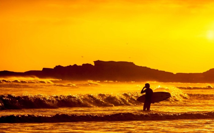 Destinations Worth Dreaming Image: A surfer stands in the ocean observing waves. We see little more than the silhouette because the sunlight is faded, and bathing everything in shades of orange and gold.