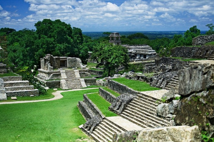 Central and South American Ruins Image: Belize's ancient city is a series of timeworn and muted greys, juxtaposed by green lawns, and jungle trees. A blue sky and white clouds complete the scene.