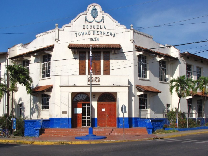 Architecture In Panama Image: Escuela Tomas Herrera is a Spanish Colonial building with red doors, and blue accents near the base of the building