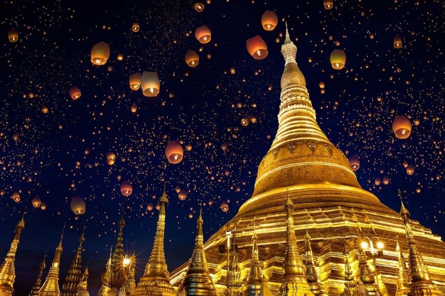 Destinations Worth Dreaming Image: Lanterns float up into the night sky past golden buildings.
