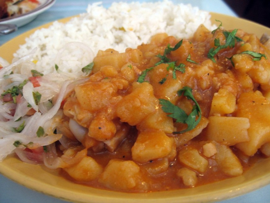Visit Peru Image: The hearty potato stew described in this section of our Peru food tour is heaped onto a yellow plate, and accompanied by white rice, and what appears to be a vegetable slaw.