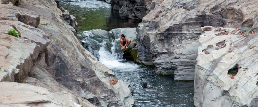 Swimming Holes Image: People perch amongst the boulders and enjoy the cool waters of this Panamanian swimming hole.