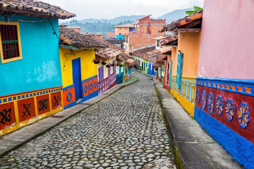Destinations Worth Dreaming Image: Photograph of a camera looking down a cobblestone street; to the left and right are brightly coloured buildings with tiled roofs.