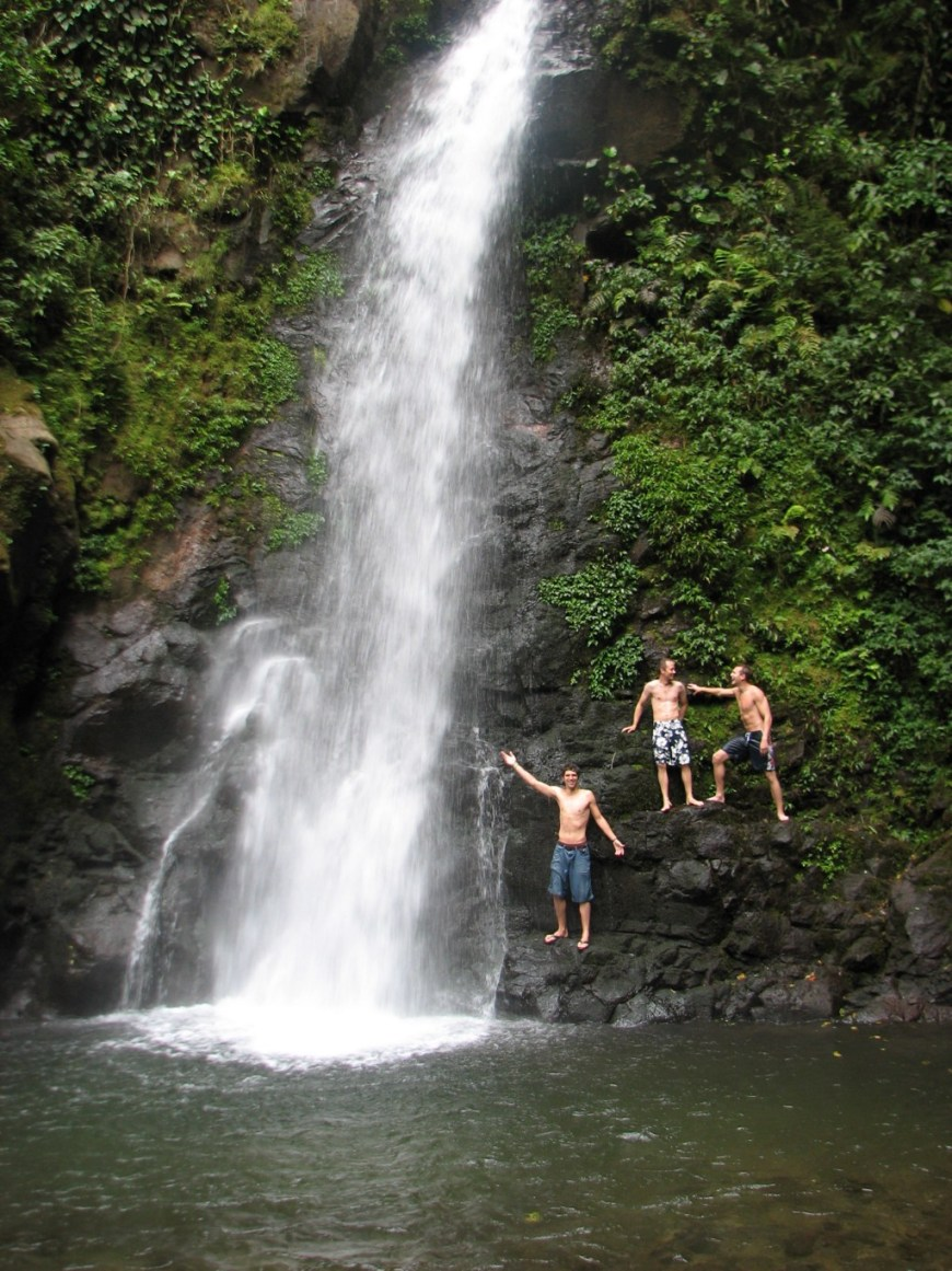 Swimming Holes Image: Three young men in swim shorts pose near the foot a swimming hole that has a waterfall pouring into it.