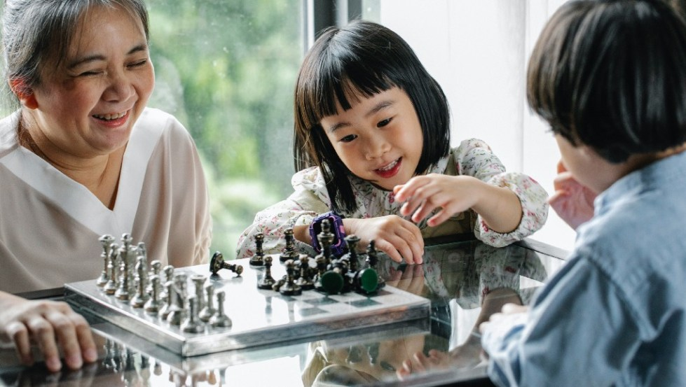 An older woman playing chess with two young children
