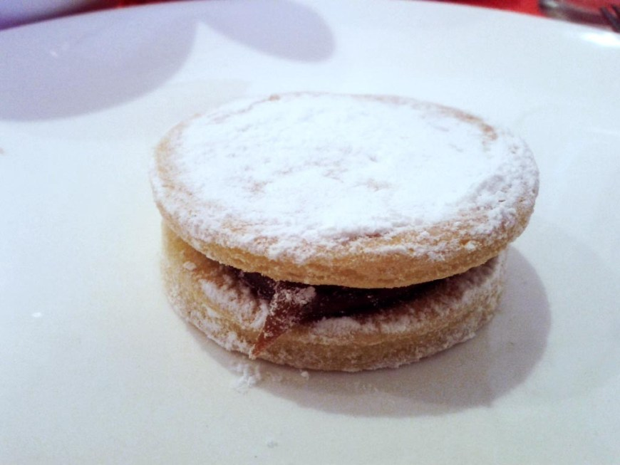 Visit Peru Image: A single alfajores sits on a white plate, and has been dusted with a generous amount of powdered (or confectioner's) sugar.