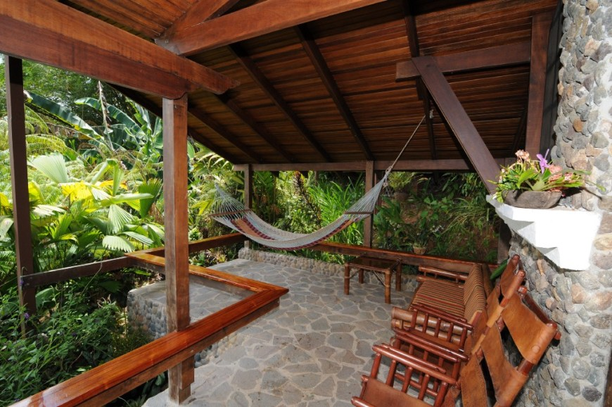Eco-Friendly Costa Rica Image: A stony veranda has chairs, and a hammock in the corner which looks like a lovely place to read a book or take a nap.