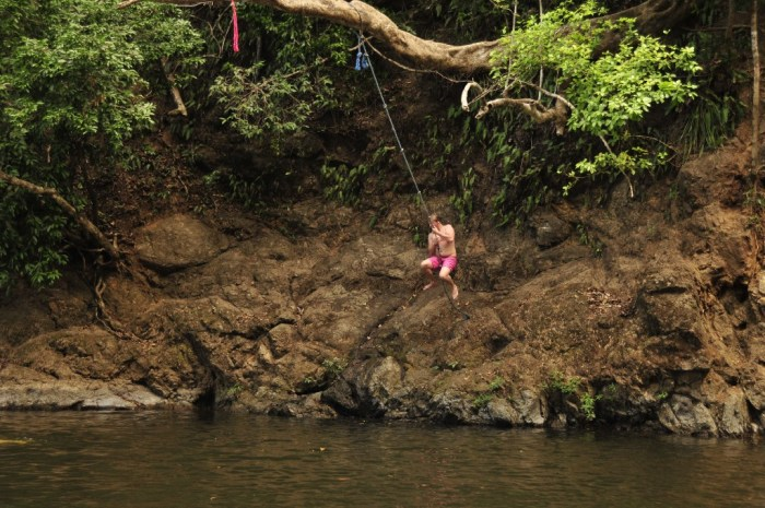 Swimming Holes Image: A young man in red swim shorts prepares to jettison himself off of rocks to swing on a rope suspended from a tree branch, and plunge into the water below.