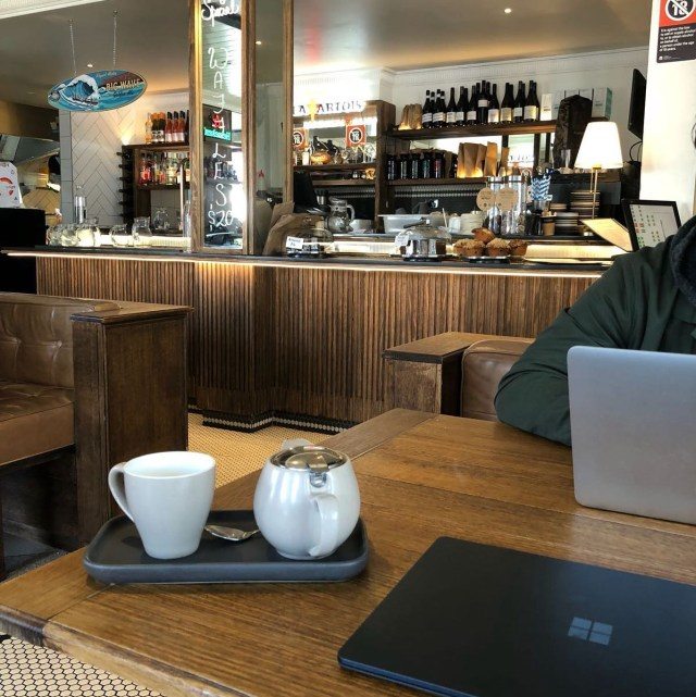 working at a café with laptop and coffee