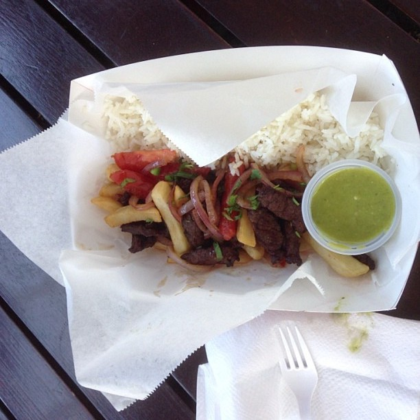 Visit Peru Image: A to-go basket is filled with the colourful beef and vegetable stir-fry has fluffy white rice on the side, and fried potatoes throughout. A green dipping sauce sits in the basket, and a napkin and white plastic fork are off to the side.