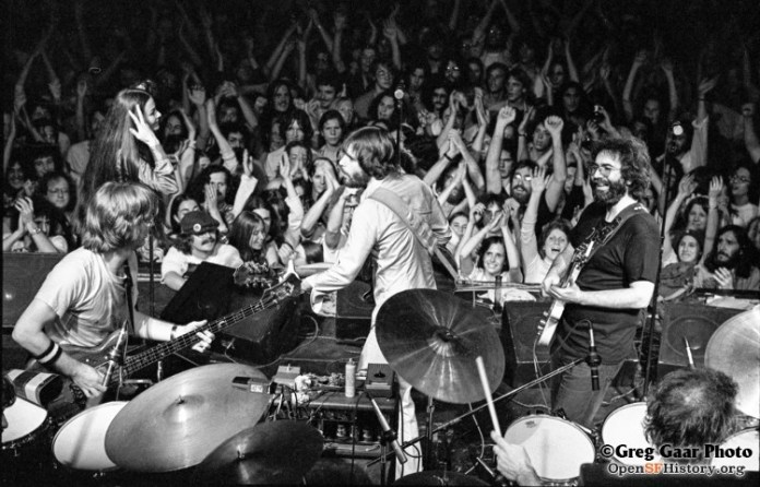 Black and white photo of The Grateful Dead on stage with an audience of fans in the background.