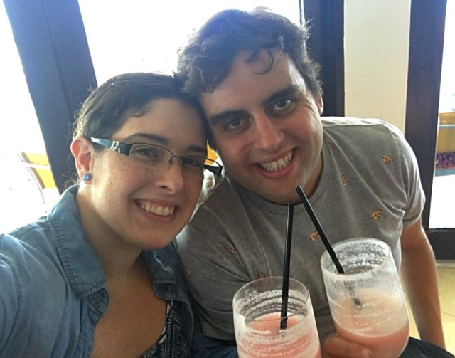 My husband and I at the bar with our drinks, pizza shirt, drinks, pina colada with some strawberry flavor