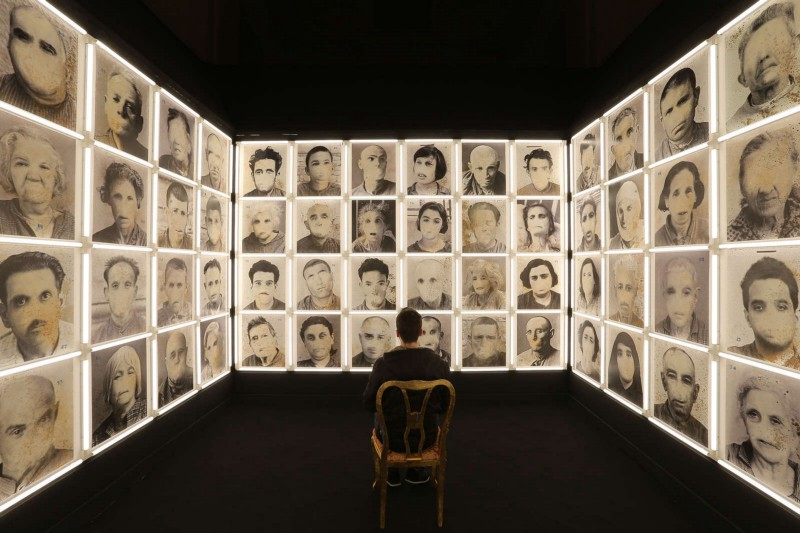 A man sitting in the middle of a room in an installation depicting madmen without a mouth, in the museum of madness.