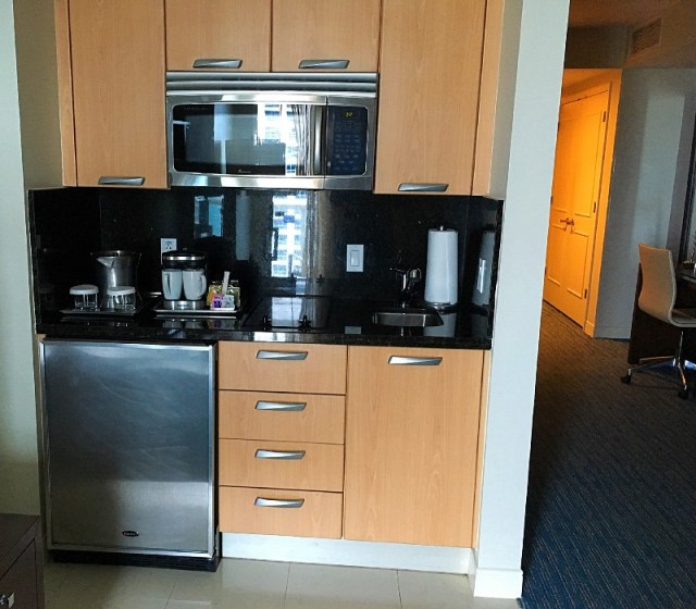 The Kitchenette, microwave, sink, two heating elements, coffee maker, mugs, ice bucket, glasses, mini refrigerator, drawers, paper towels