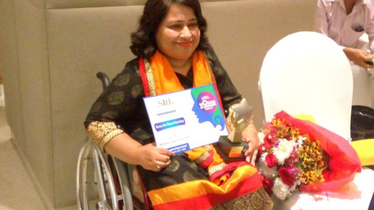 Description: A photograph of Abha holding a certificate and a trophy, and smiling at the camera. She is sitting on her wheelchair and beside her is a chair with a bouquet of flowers.