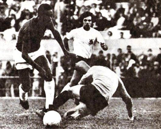 Enéas, acompanhado por Cláudio Marques, dribla o goleiro Luís Antônio e marca o quinto gol da Lusa na vitória por 5×1 no estádio do Pacaembu