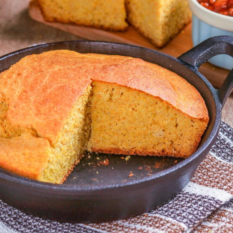 A big hunk of cornbread in a cast-iron skillet.