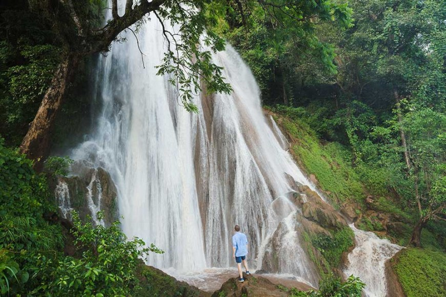 Destinations Worth Dreaming Image: A male traveller wearing dark-blue shorts and a light-blue shirt stands on a rock observing a waterfall as it rushes and breaks down a slope in—streaming into white channels.