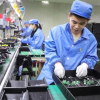Employees work on photovoltaic products at a renewable energy company in Tonglu, China, on Wednesday. China will overtake the United States to become the world's biggest economy in 2028, five years earlier than previously estimated due to the contrasting recoveries of the two countries from the COVID-19 pandemic, a think tank said. | AFP-JIJI