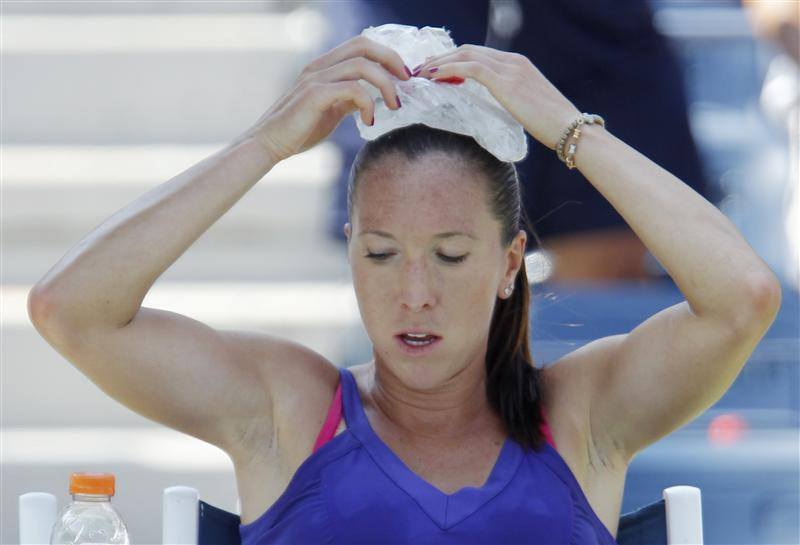 Jelena Jankovic of Serbia holds an ice pack on her head during her match against Simona Halep of Romania  during the U.S. Open tennis tournament in New York