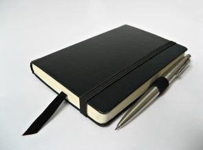 A moleskine journal and pen