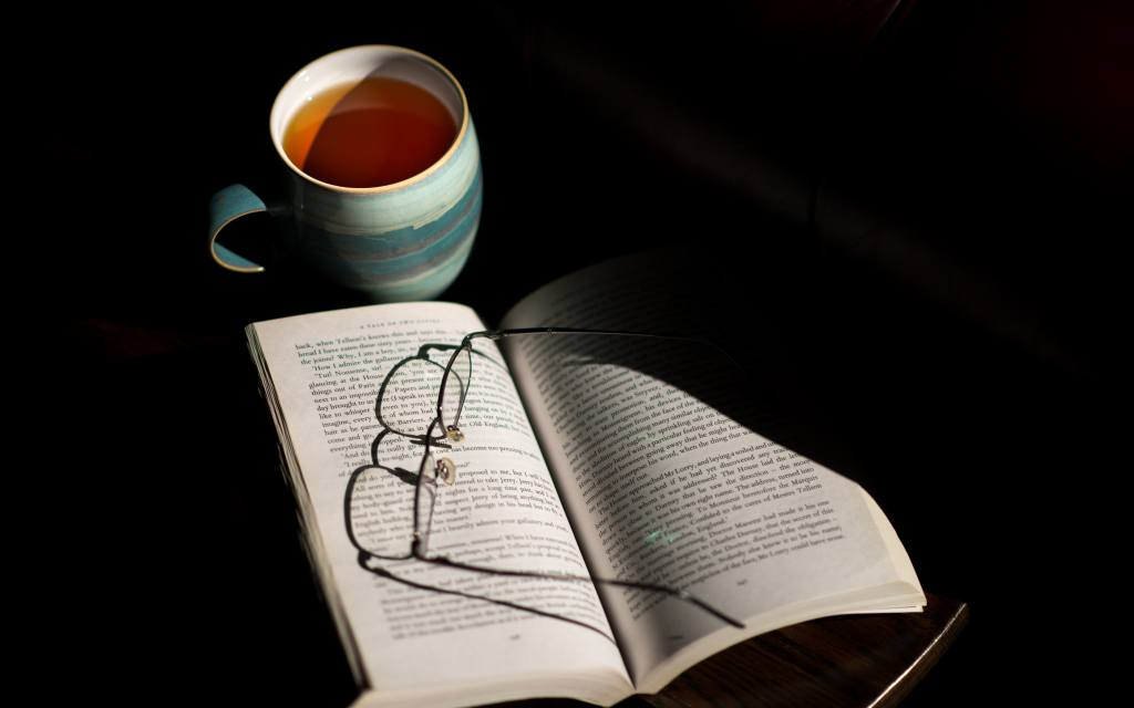 Reading Glasses On Book With Hot Tea Drink