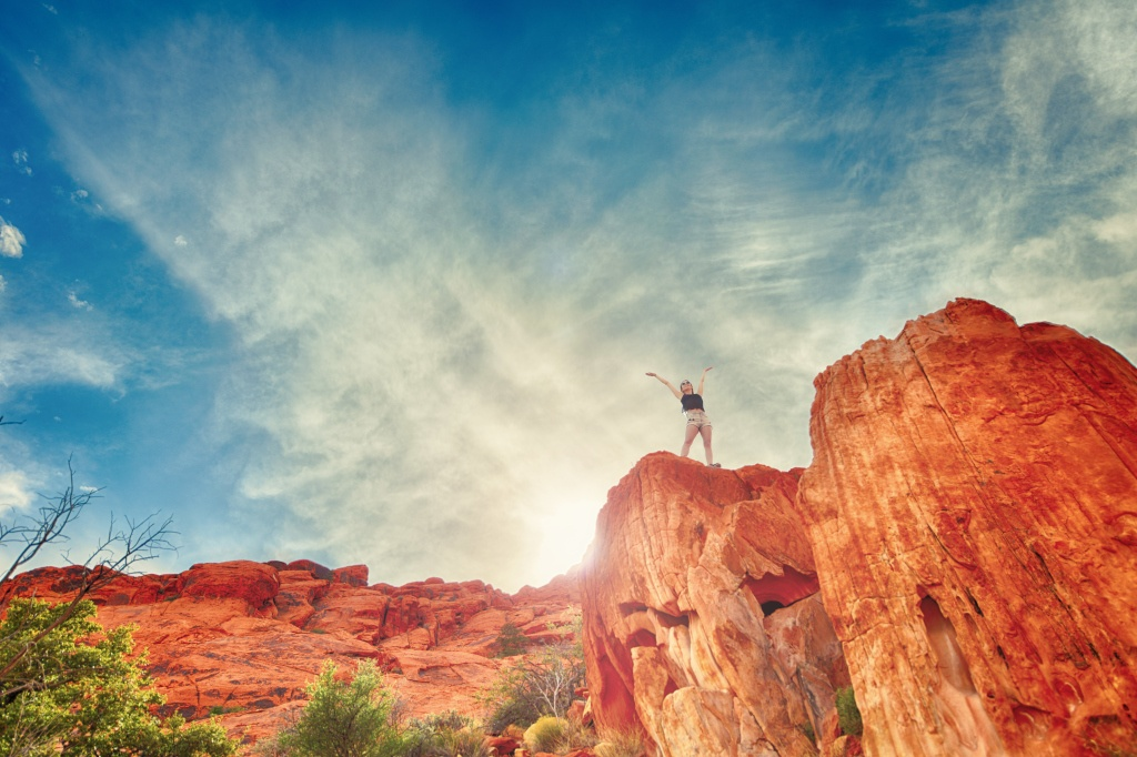 Woman Standing On Red Rocks Celebrating Success
