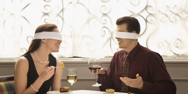 Mid adult Caucasian couple dining in a restaurant with blindfolds over eyes.