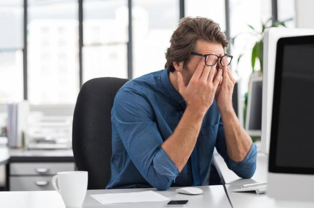 Tired businessman at desk rubbing eyes, due to headache and fatigue.