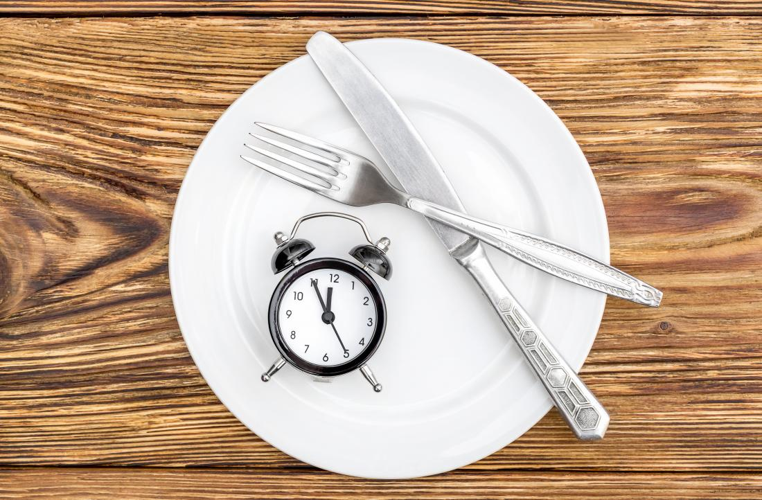 Empty plate on wooden table with knife and fork and alarm clock