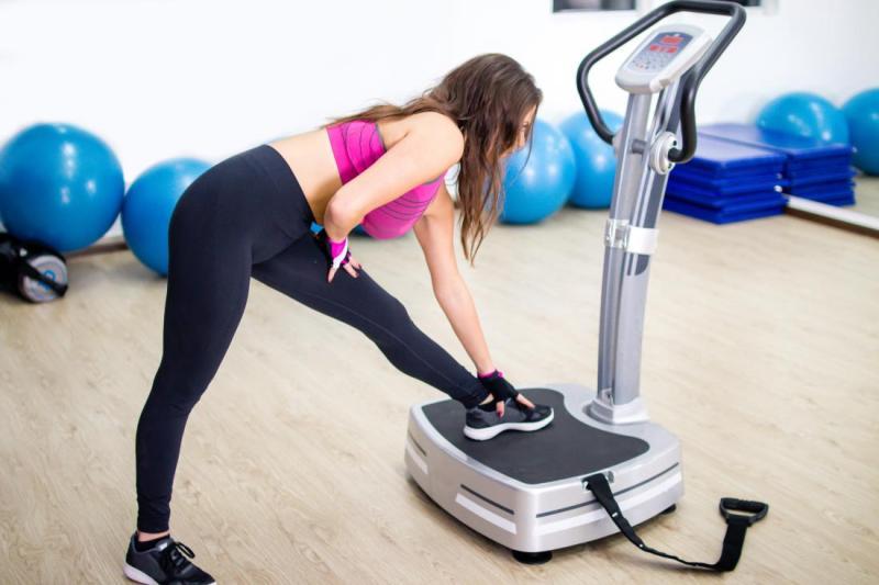 woman stretching on vibrating machine