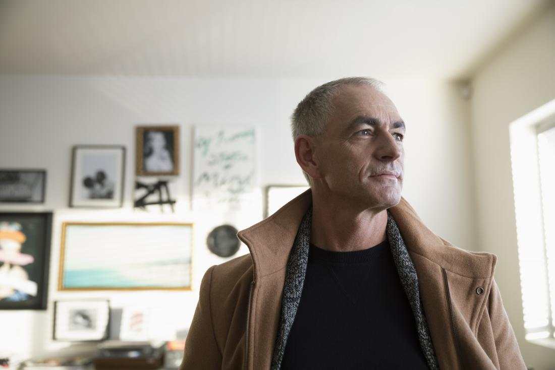 mature man with frontotemporal dementia standing in house looking thoughtful