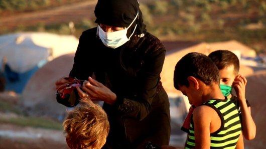 سيدة تحيك كمامات لأطفالها في مخيم _سنجار كهربا_ قرب سرمدا تصوير جابر عويد (خاصة)(1).jpg